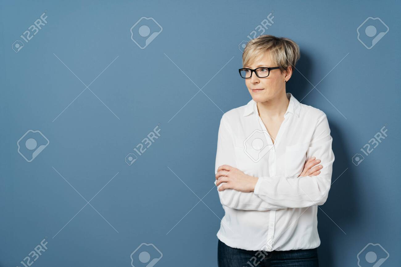 Middle-aged woman with short blond hair, wearing white blouse, standing with crossed hands and looking aside at copy space on plain blue studio background - 153539069