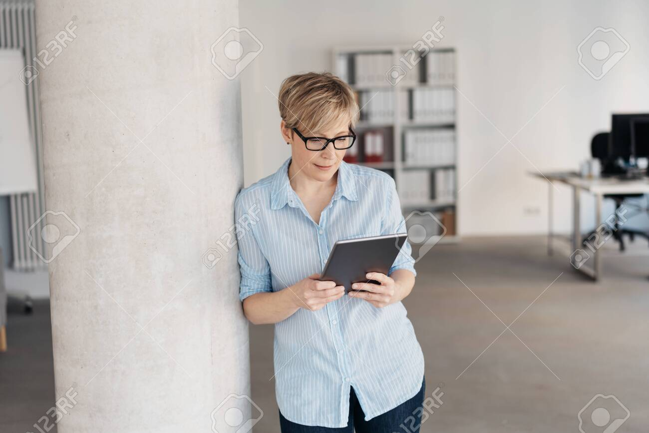 Relaxed woman standing reading on a tablet pc in a bright spacious open plan office with an engrossed expression, with copy space - 153538739