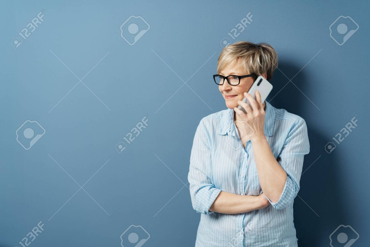 Middle-aged woman with short blond hair, in glasses and blue shirt, standing and looking aside while talking by the phone. Half-length front portrait against blue background in studio with copy space - 153539388