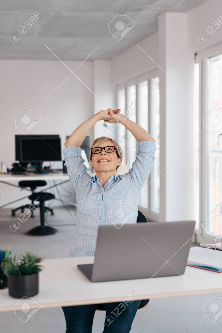 Happy businesswoman stretching her arms above her head with a beaming smile seated at a laptop in a high key office with copy space - 153539467