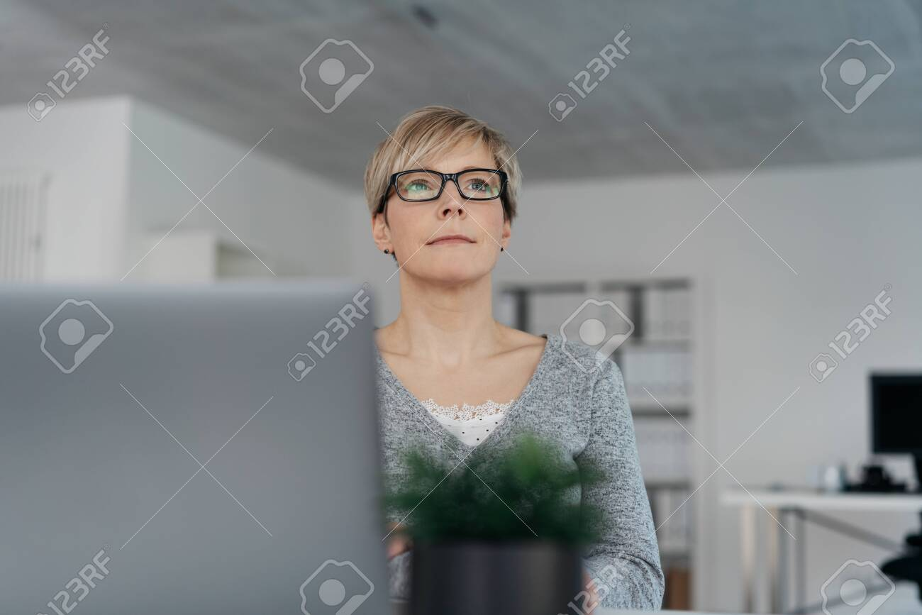 Thoughtful troubled businesswoman wearing glasses seated at her desk behind a laptop computer in a low angle view past a potted plant - 153539171