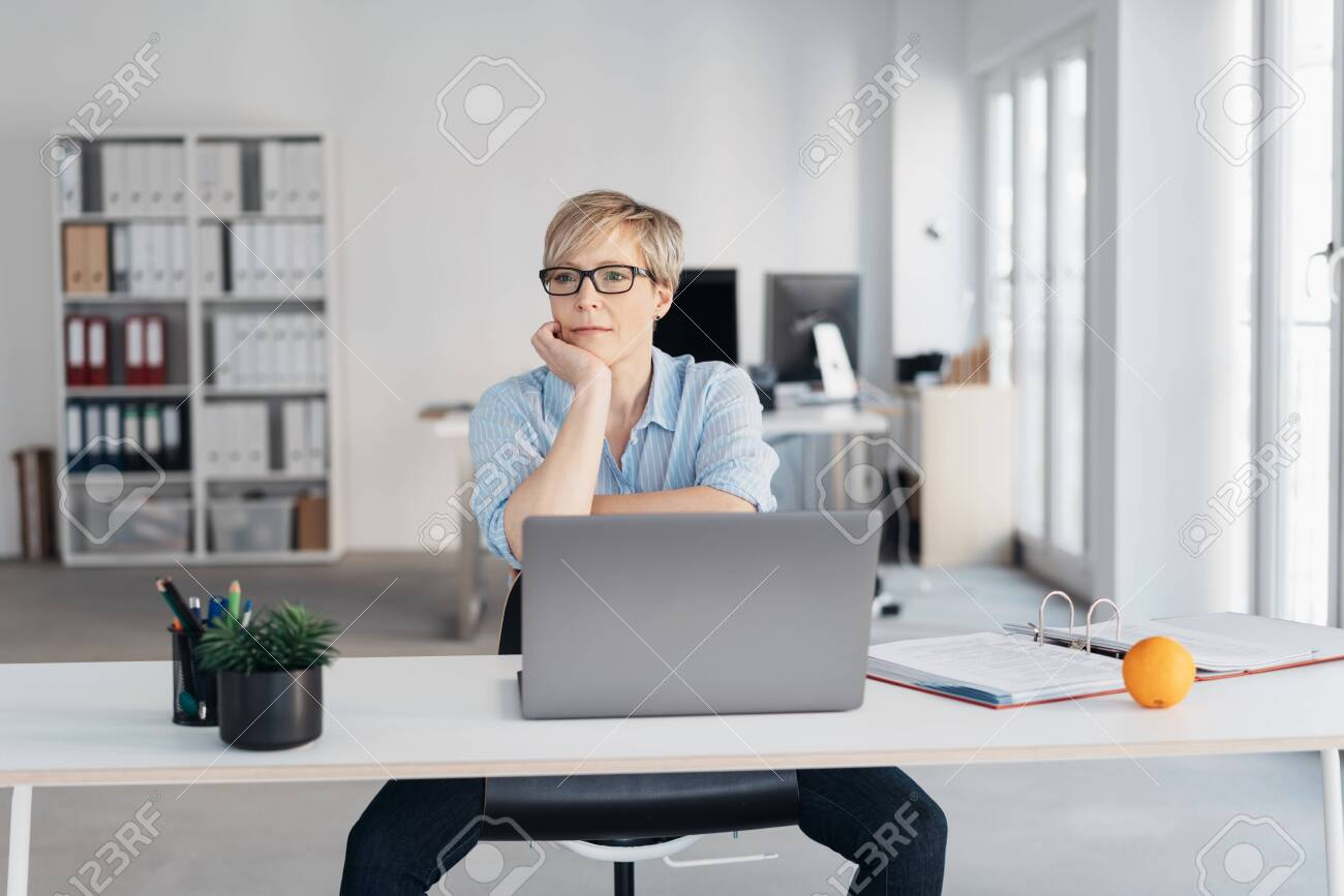 Middle-aged woman with short haircut and in glasses, sitting at laptop in empty office and thinking with sad face, propping her chin with her hand. Front portrait with copy space - 153539139