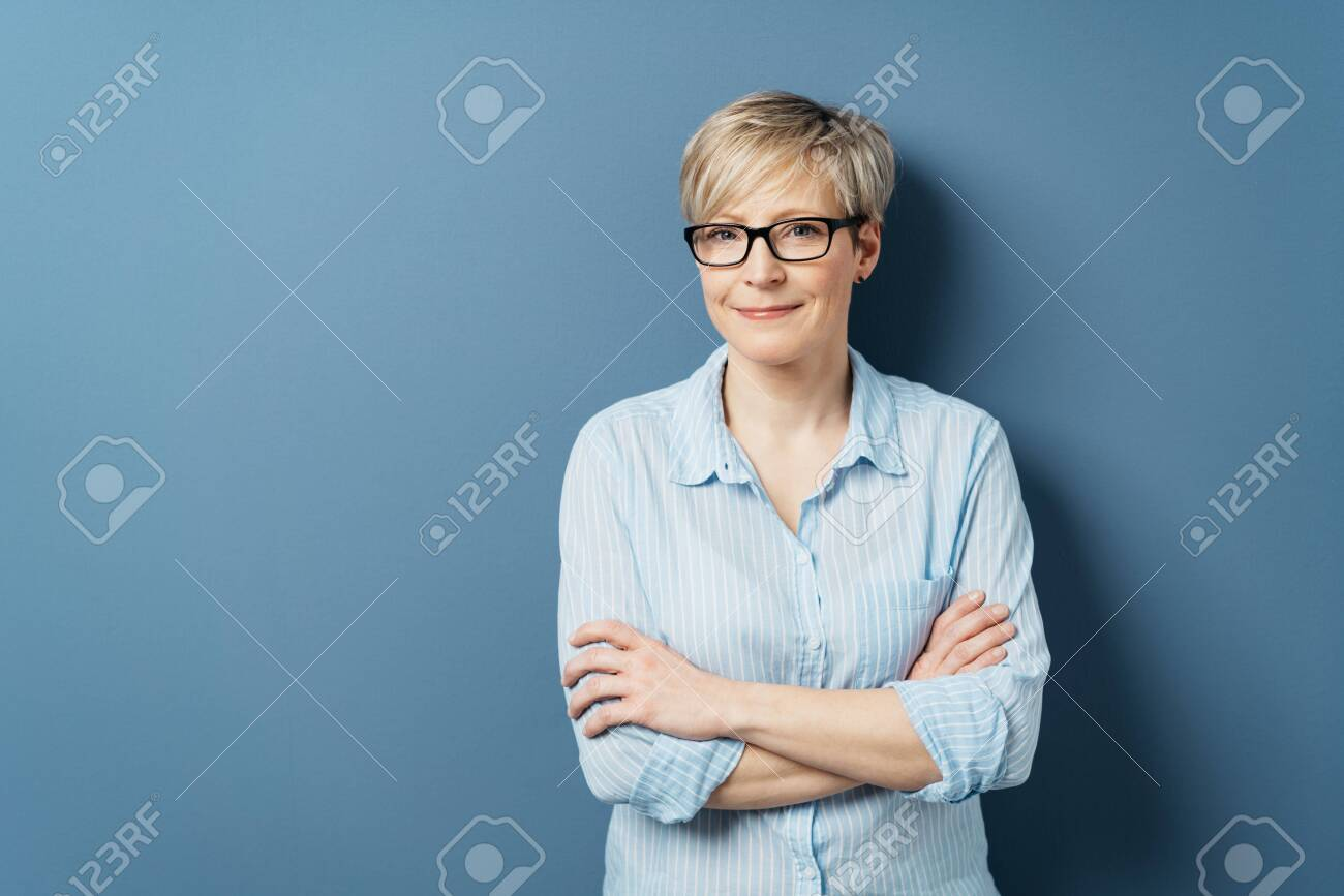 Middle-aged woman with short blond hair, in blue shirt and wearing glasses, standing with her arms crossed and looking at camera with modest smile. Half-length front portrait on blue with copy space - 153539414
