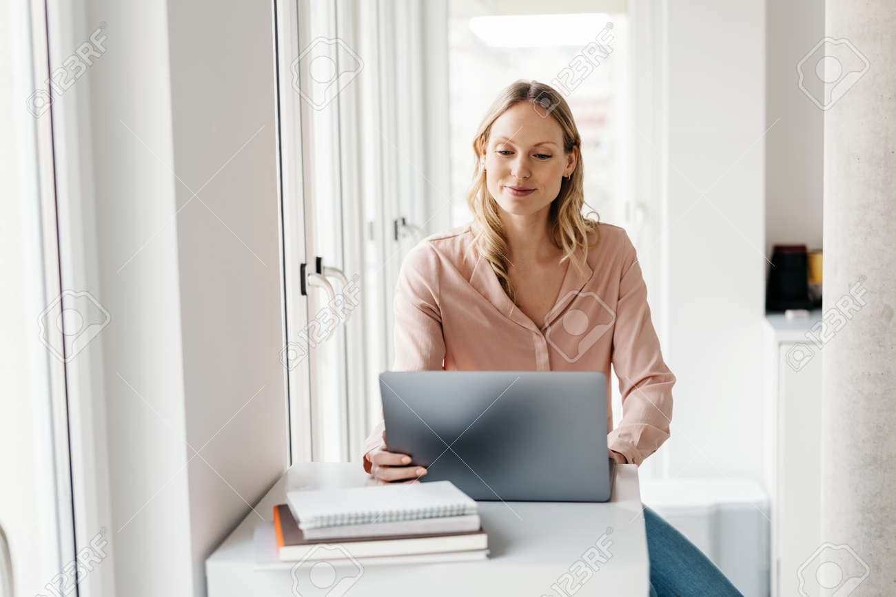 Happy young businesswoman working from home or telecommuting during the lockdown for te Covid-19 pandemic in a high key apartment with copyspace - 167565776
