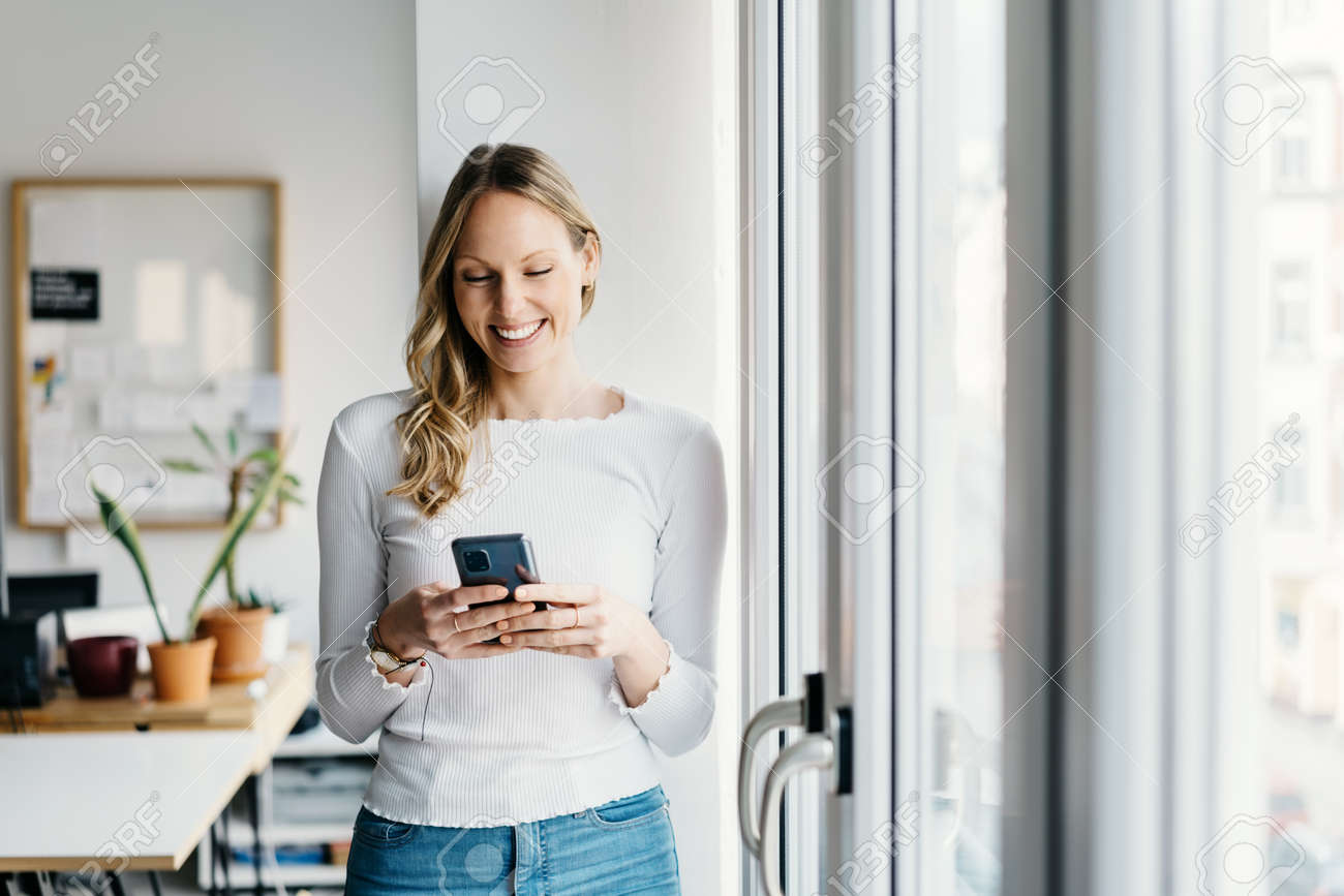 Young business woman reading a text message on her mobile with a beaming smile of pleasure as she stands in a bright office relaxing near a window with copyspace - 167565780