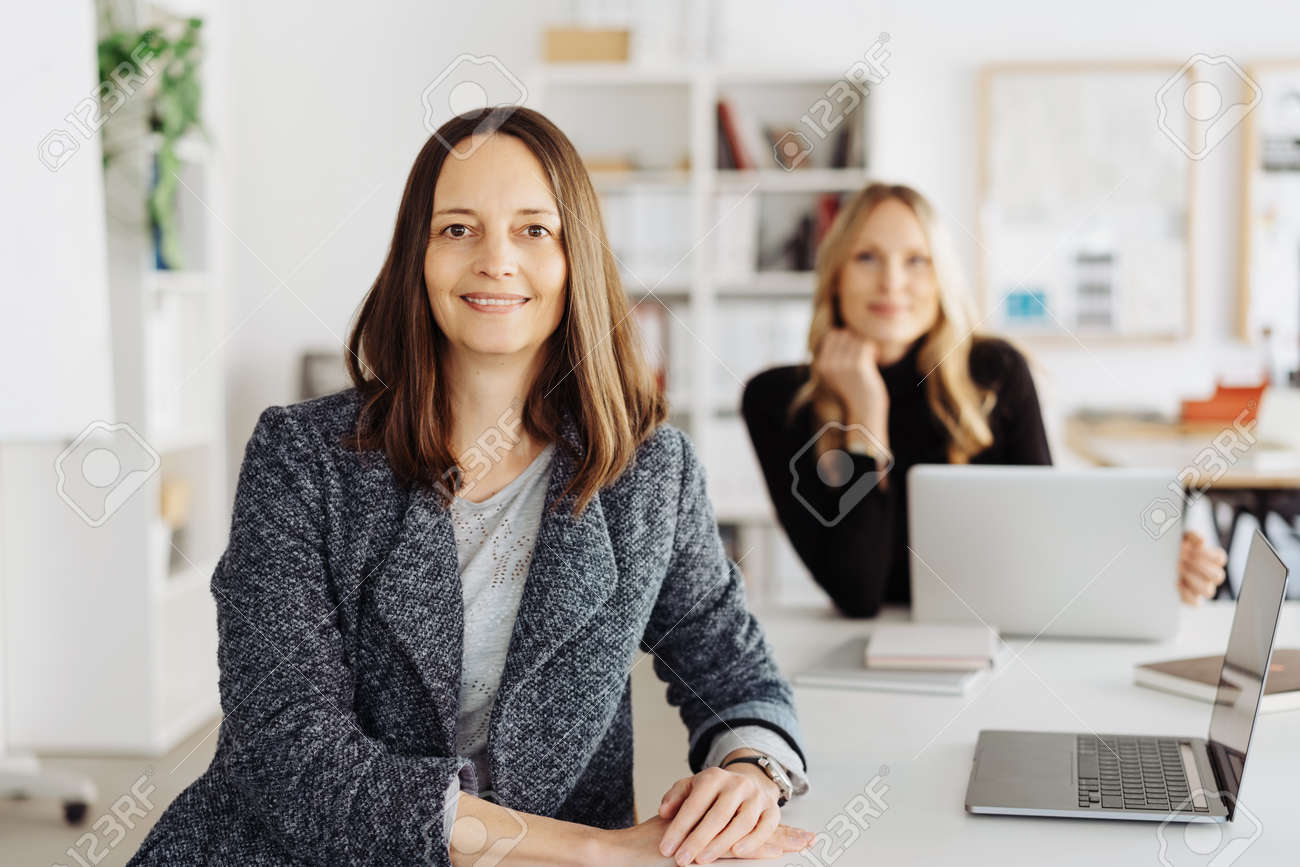 Smiling confident attentive smart middle-aged businesswoman turning to look at the camera watched by a female colleague working at a laptop in the background in a modern office - 167021653