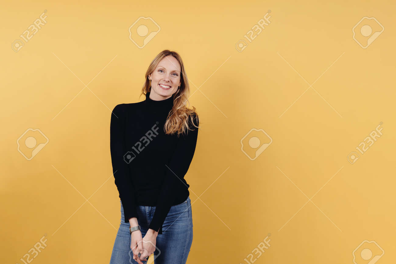 Cute vivacious young woman with long blond hair wearing jeans and a black turtle neck posing over a colorful yellow studio background with copyspace - 167021251