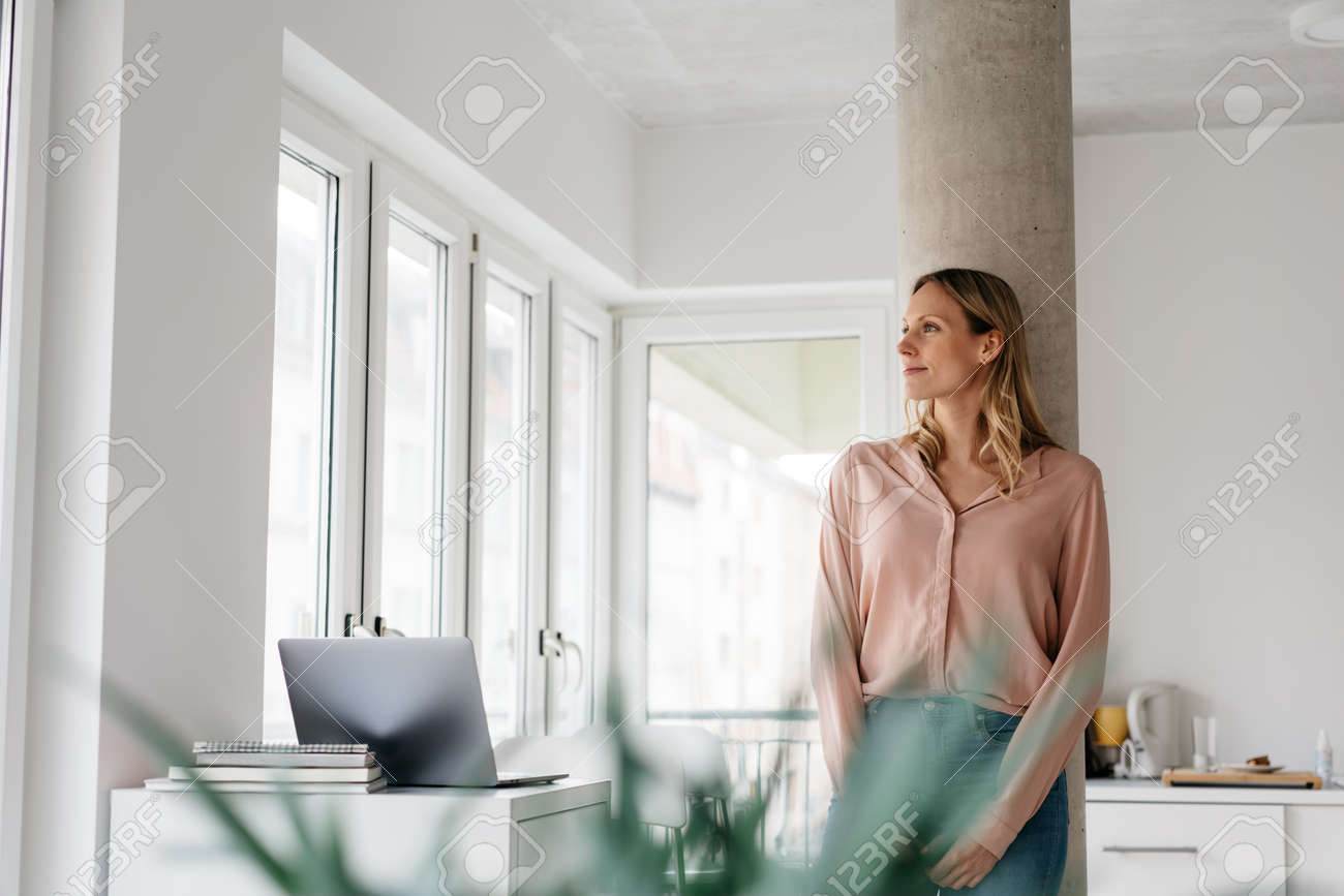Young woman working from home during the Covid-19 pandemic standing daydreaming looking aside through a window with a quiet smile in a high key room with copyspace - 167565782