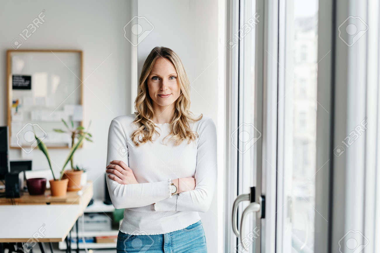 Confident friendly young woman watching the camera with folded arms as she stands alongside a bright window in a spacious office smiling happily - 167021436