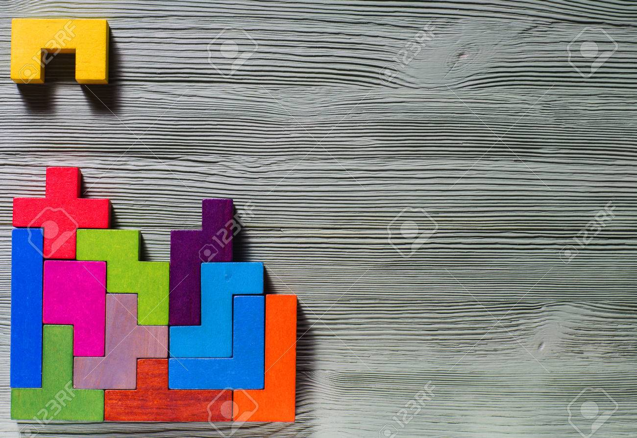 The concept of logical thinking. Geometric shapes on a wooden background. Tetris toy wooden blocks. - 69025233