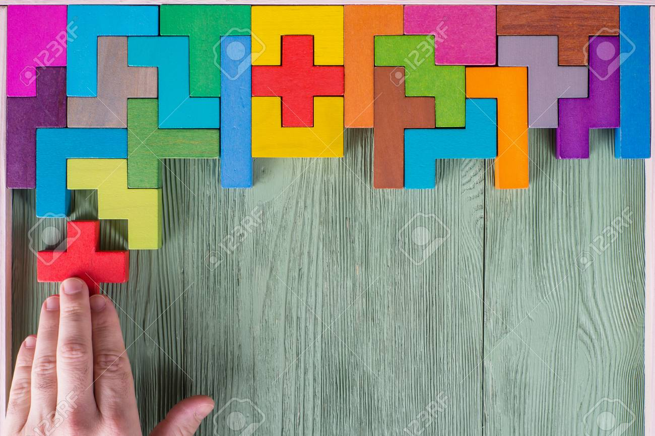 Concept of decision making process, logical thinking. Logical tasks. Conundrum, find the missing piece of the proposed. Hand holding puzzle element. Background with colorful shapes wooden blocks - 91696294