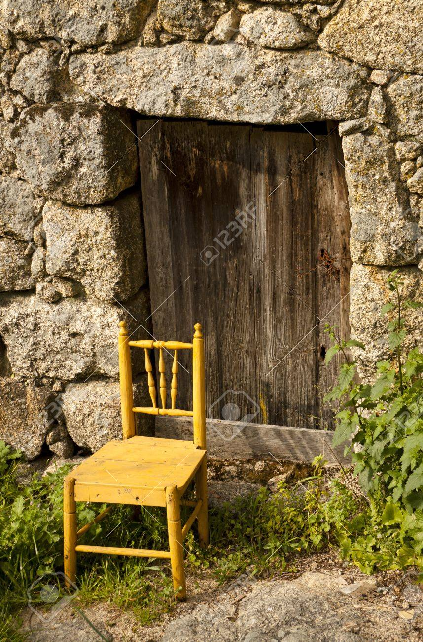 Door of an ancient house with a chair in the entrance Stock Photo - 9386217