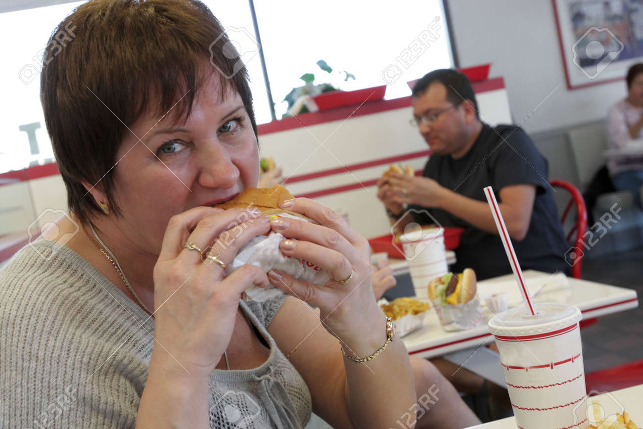 The hungry woman eats burger in a snack bar Stock Photo - 5204641