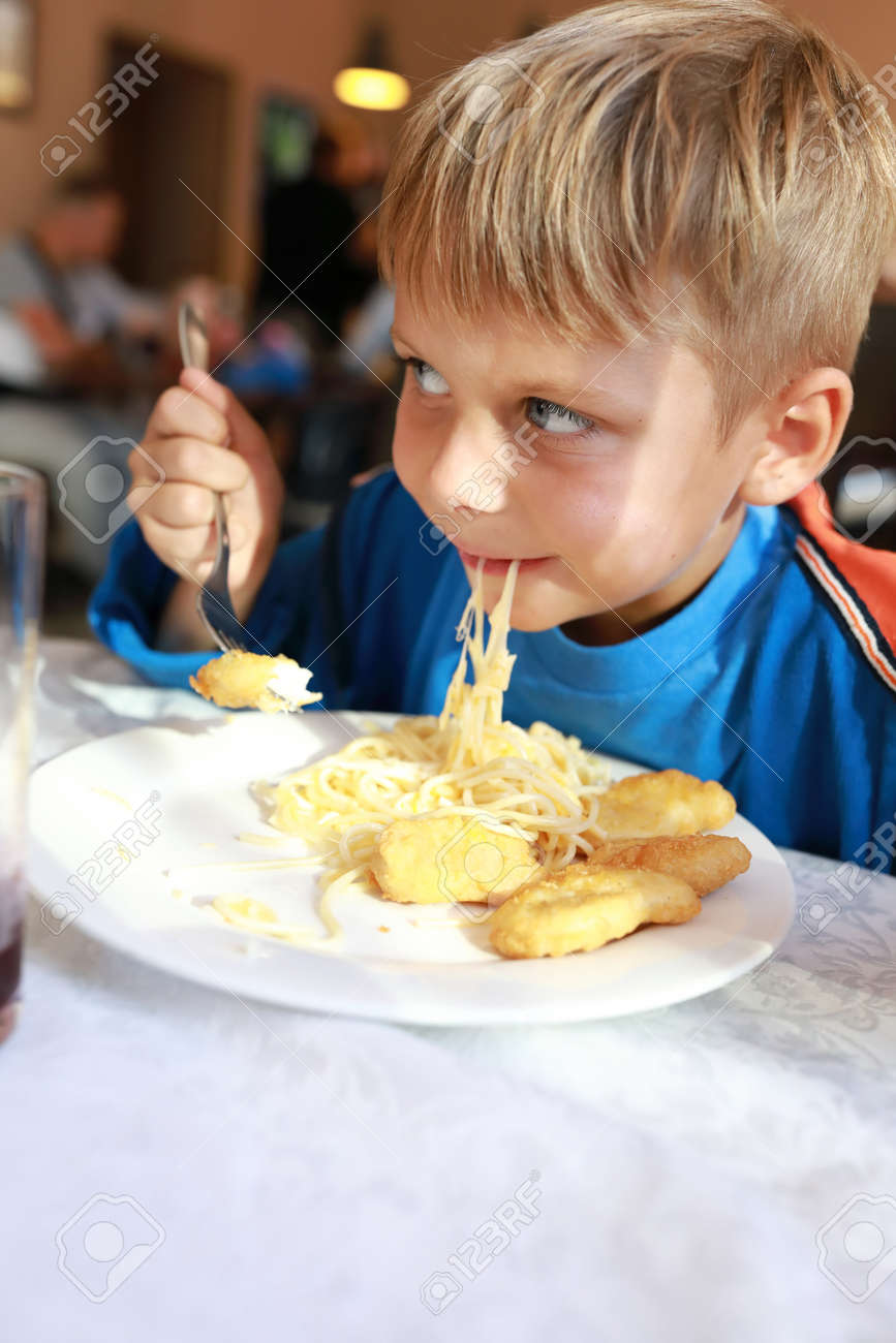 Child eating spaghetti with nuggets in restaurant - 155372755