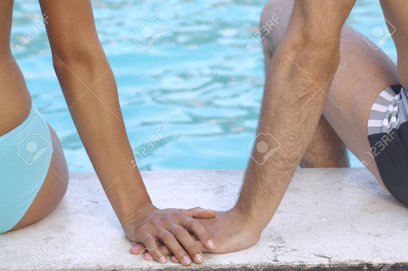 Couple at side of pool holding hands stock photo 86060701