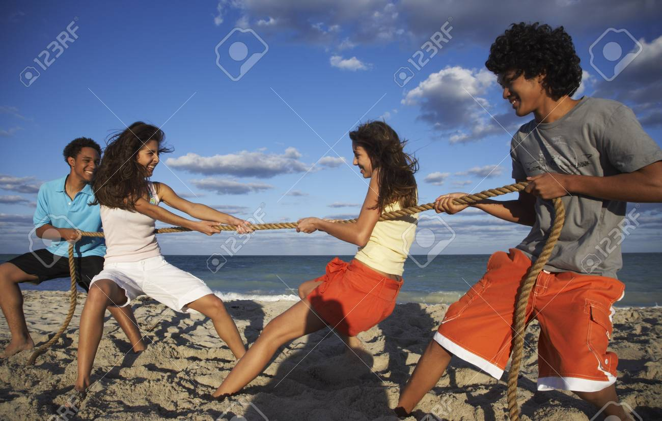 Friends Playing Tug Of War On Beach Stock Photo 86238081