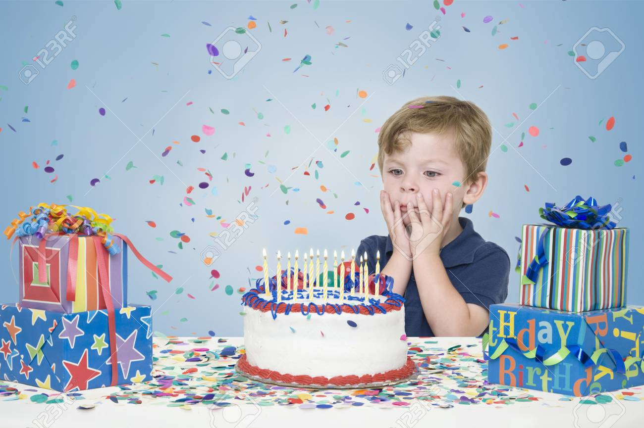 Young Boy With Birthday Presents And Making A Wish Before Blowing