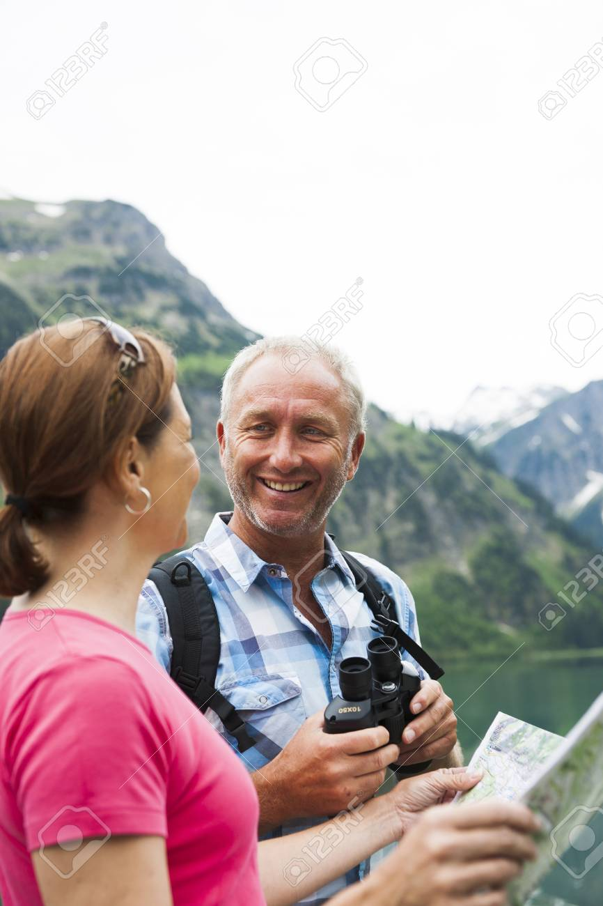 Close Up Of Mature Couple Looking At Map Hiking In Mountains Lake