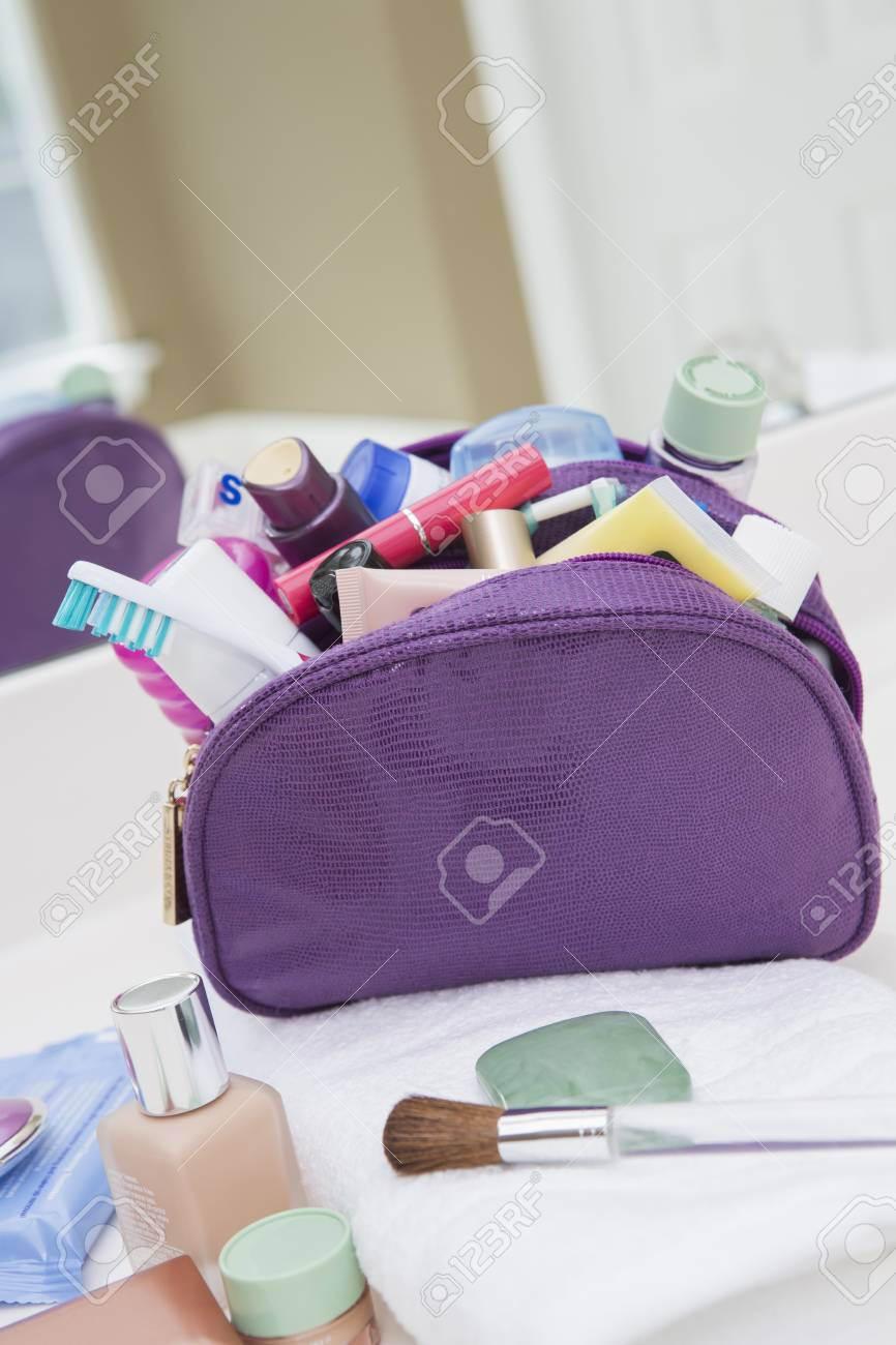 Women's toiletry, cosmetic travel bag on bathroom counter, filled