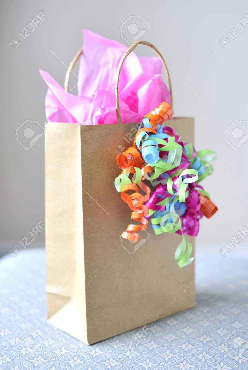 still life of a brown paper, gift bag with pink tissue paper.. stock