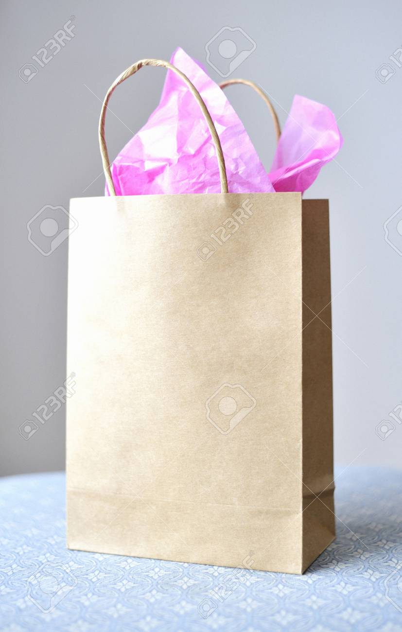 still life of a brown paper, gift bag with pink tissue paper