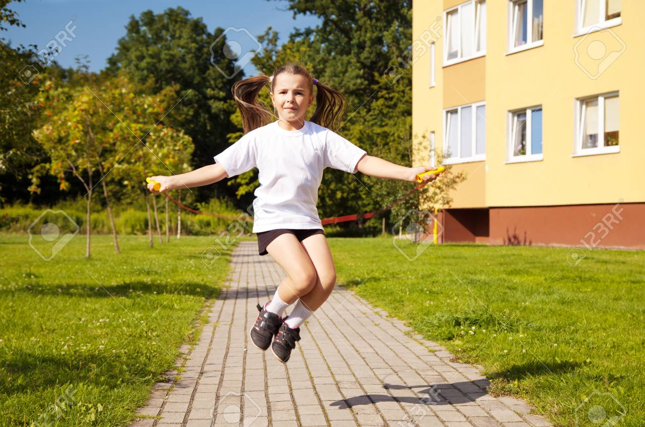 acc1ff76 little girl in white shirt and black shorts jumping rope outside Stock  Photo - 43626157