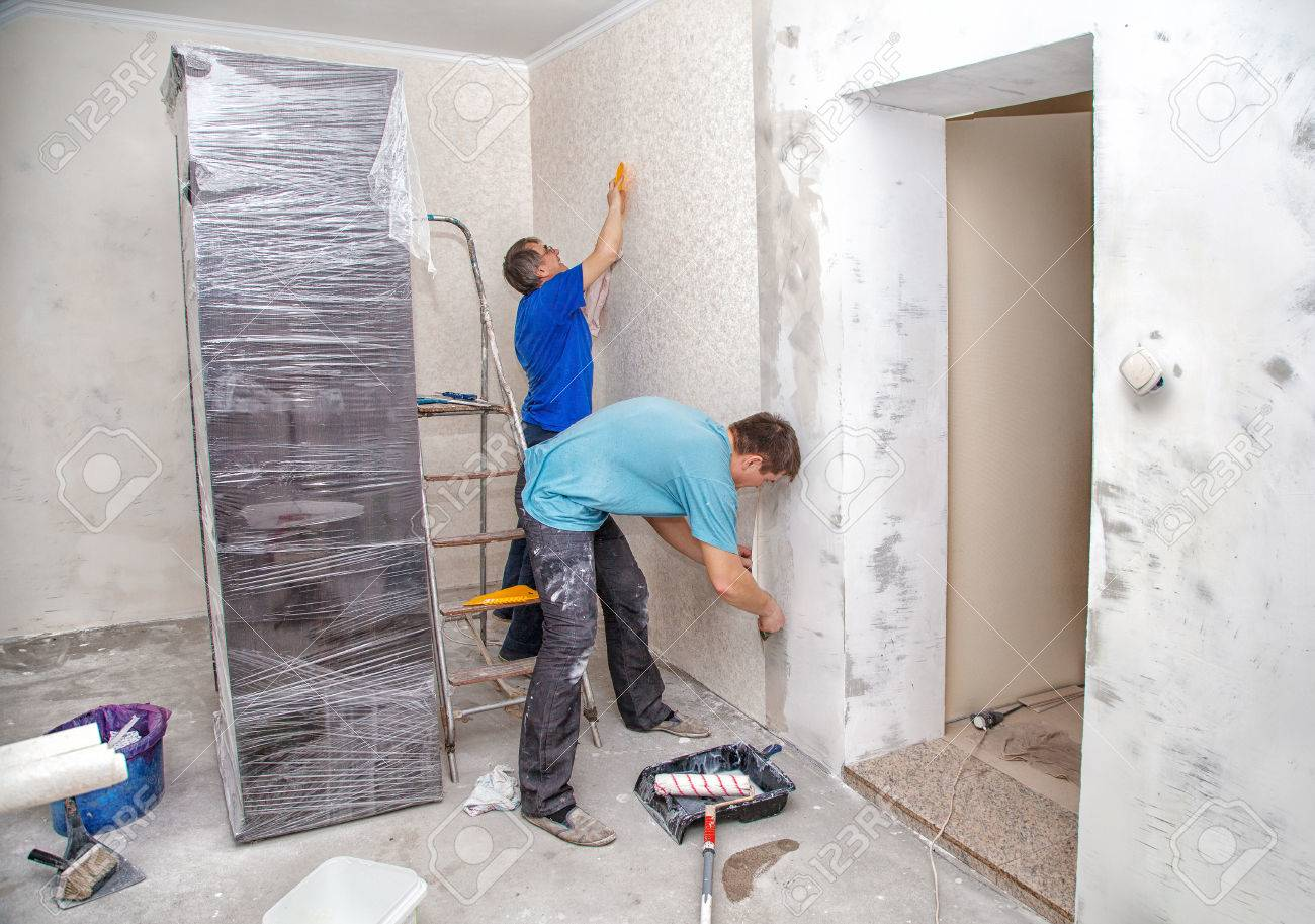 Two Men Applying Wallpaper On Wall In New Home