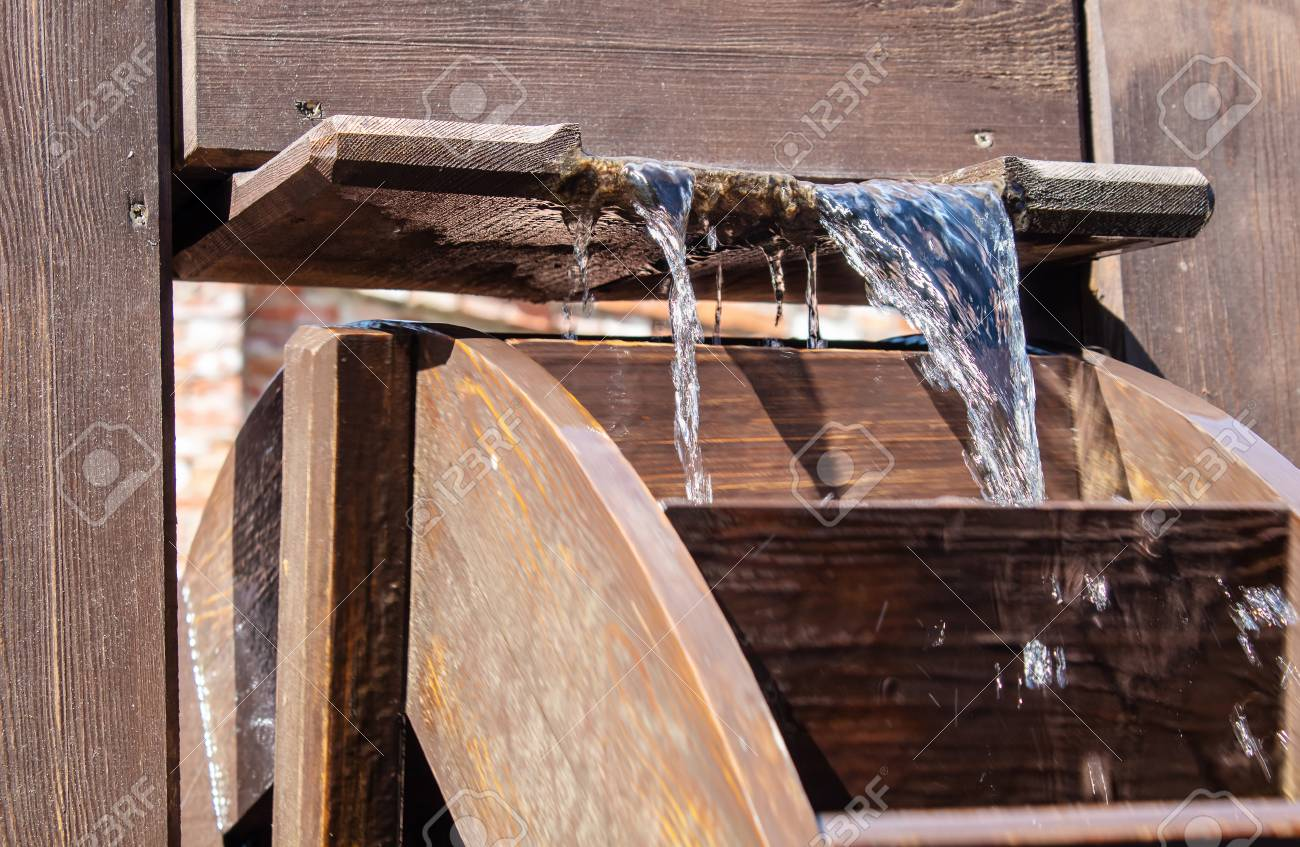 Large Wooden Wheel Rotating With Water Outdoor Closeup On Sunny