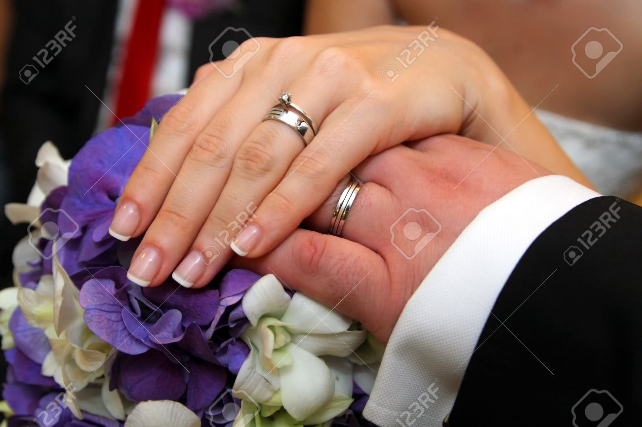 Bride And Groom Hands Wearing Wedding Rings Over Bride Bouquet Stock