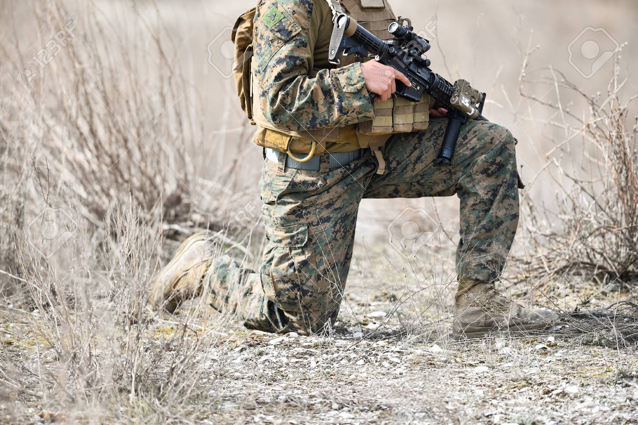 automatic rifle detail and military camouflage uniform on a soldier