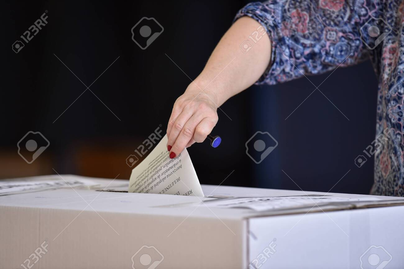 Hand of a person casting a vote into the ballot box during elections - 134838604
