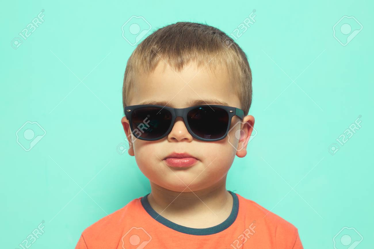 6c03aaac5415 Child wearing sunglasses with a serious attitude. Blond Kid with sunglasses  Stock Photo - 103598575