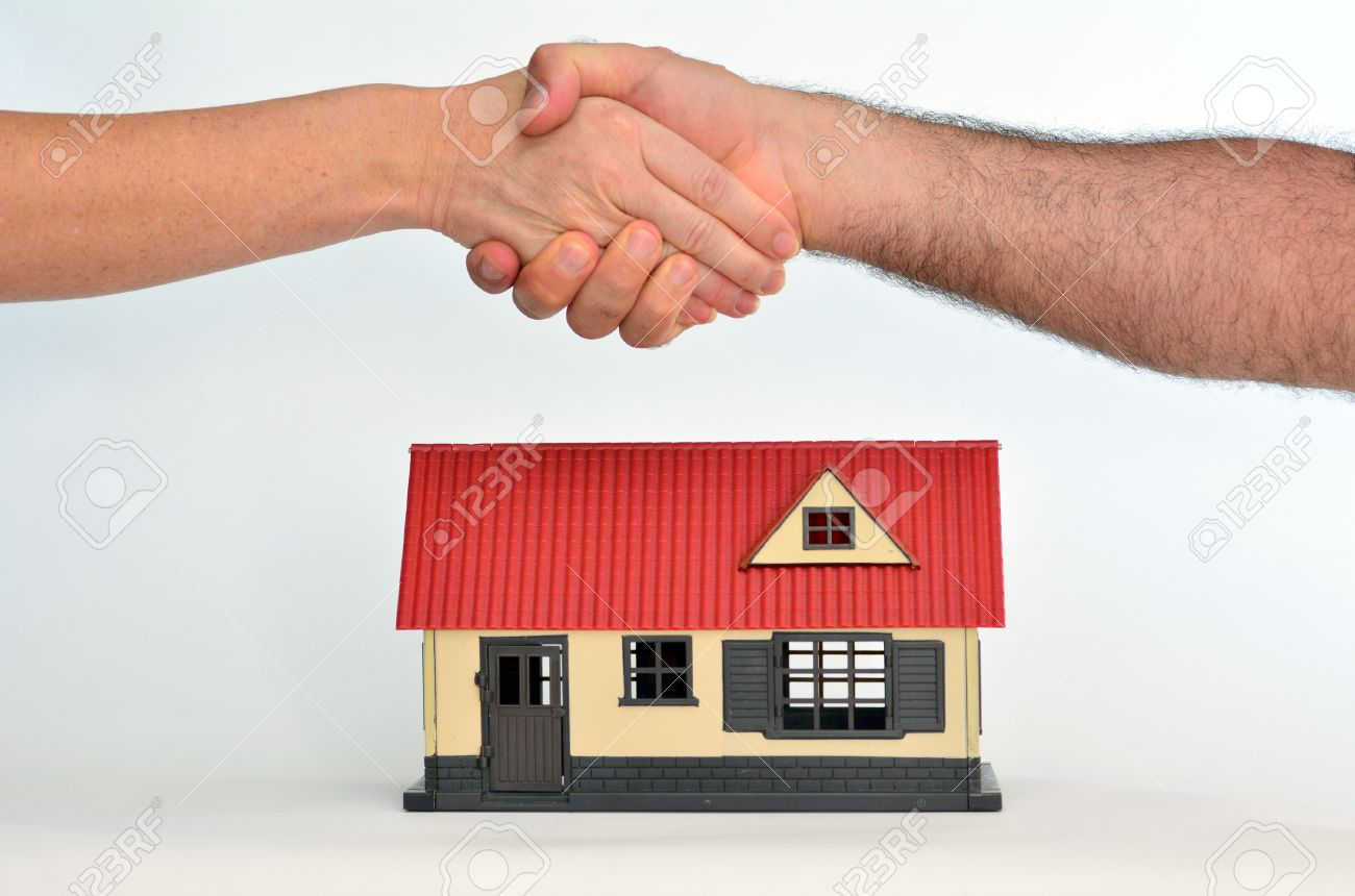 Man and a woman shaking hands over a toy house on white background - copy space.Concept photo of real estate business, home Insurance, house rental, buying, renting, mortgage, selling, finance. - 47548802