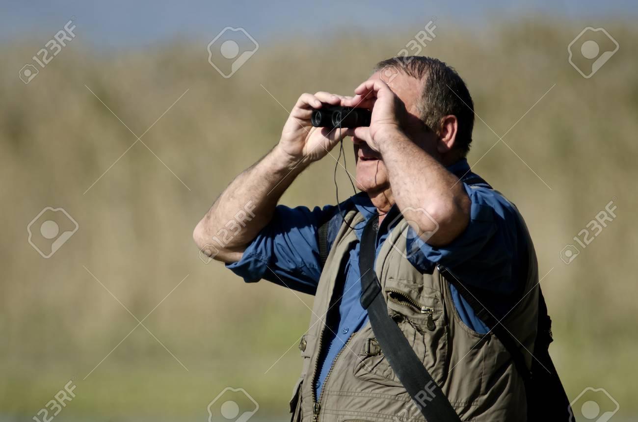Ein älterer wanderer und vogelbeobachter sucht vögel mit dem