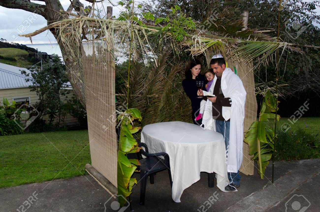 Young Jewish family prays at the Sukkah for the Jewish festival of Sukkot. A Sukkah is a temporary structure where meals are taken for the week. - 46952350