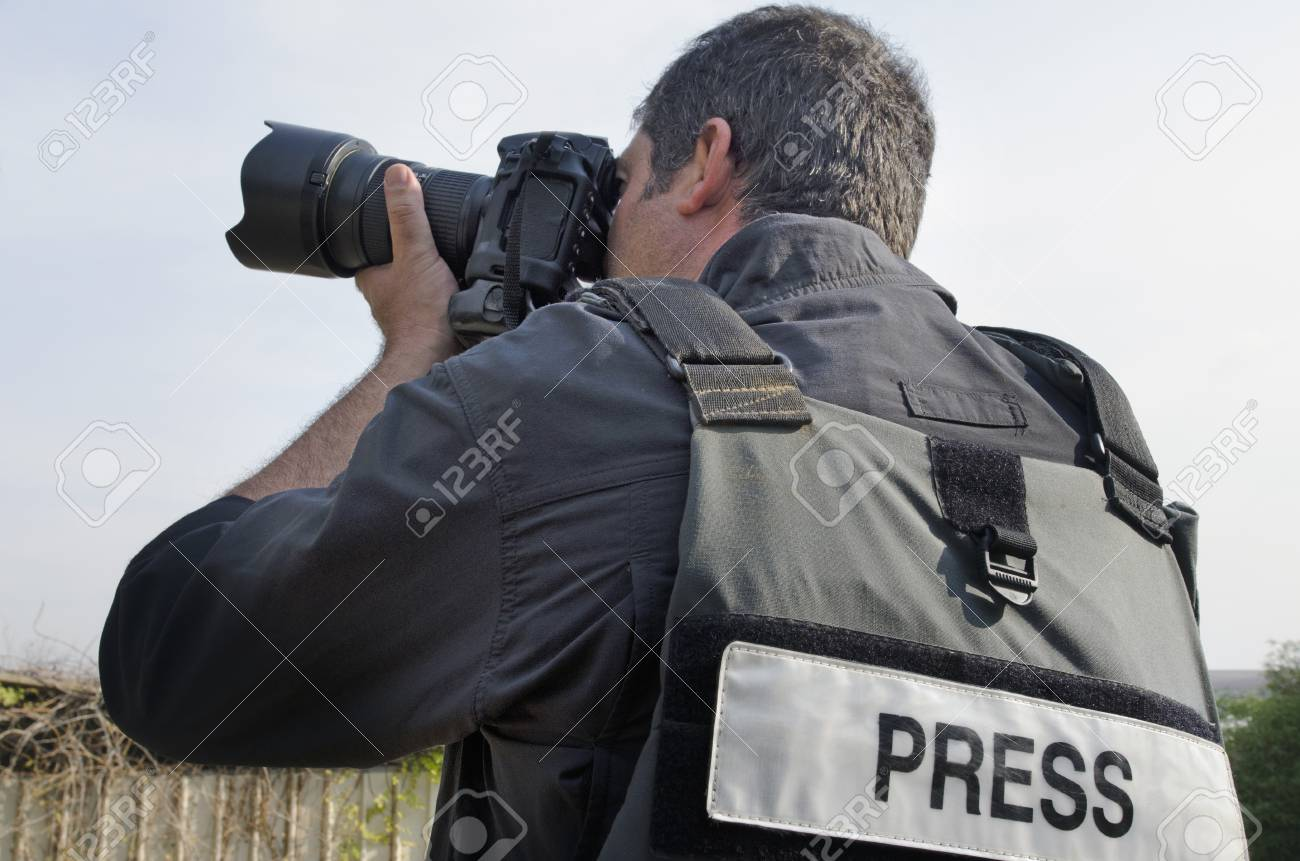 A press photographer takes photos with a professional camera - 46952424