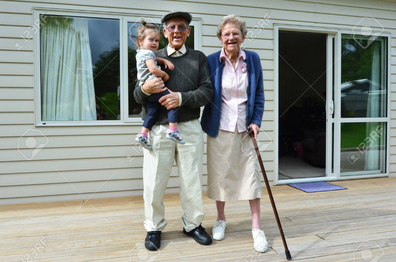 Smiling grandparents holding their grandchild outside their home. - 46952526