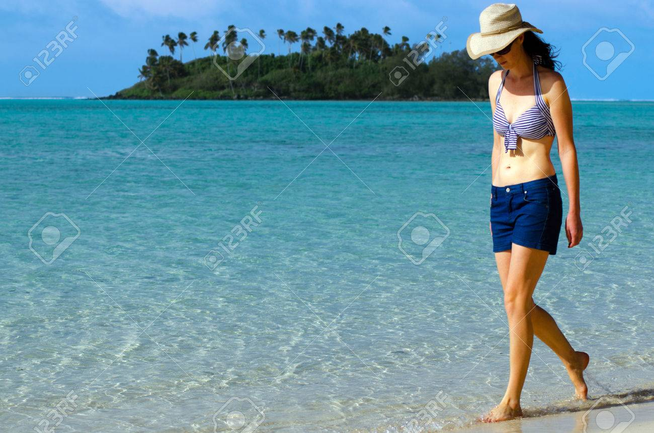 young happy woman on vacation walks on muri beach lagoon in