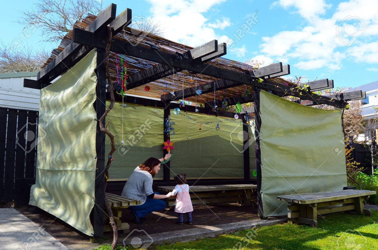 Jewish woman and child visiting their family Sukkah in the Jewish festival of Sukkot. A Sukkah is a temporary structure where meals are taken for the week. - 46575338