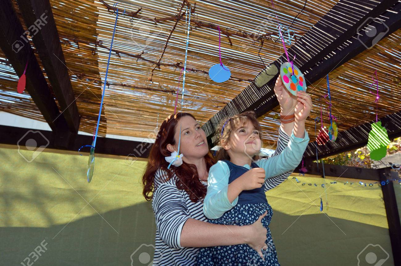 Jewish woman and child decorating their family Sukkah for the Jewish festival of Sukkot. A Sukkah is a temporary structure where meals are taken for the week. - 46575392