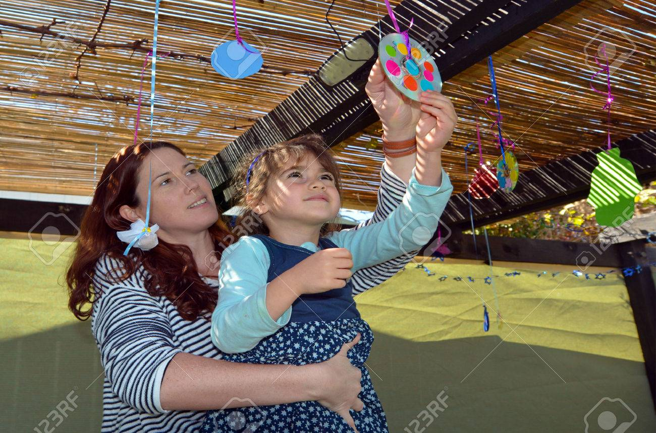 Jewish woman and child decorating their family Sukkah for the Jewish festival of Sukkot. A Sukkah is a temporary structure where meals are taken for the week. - 46575398
