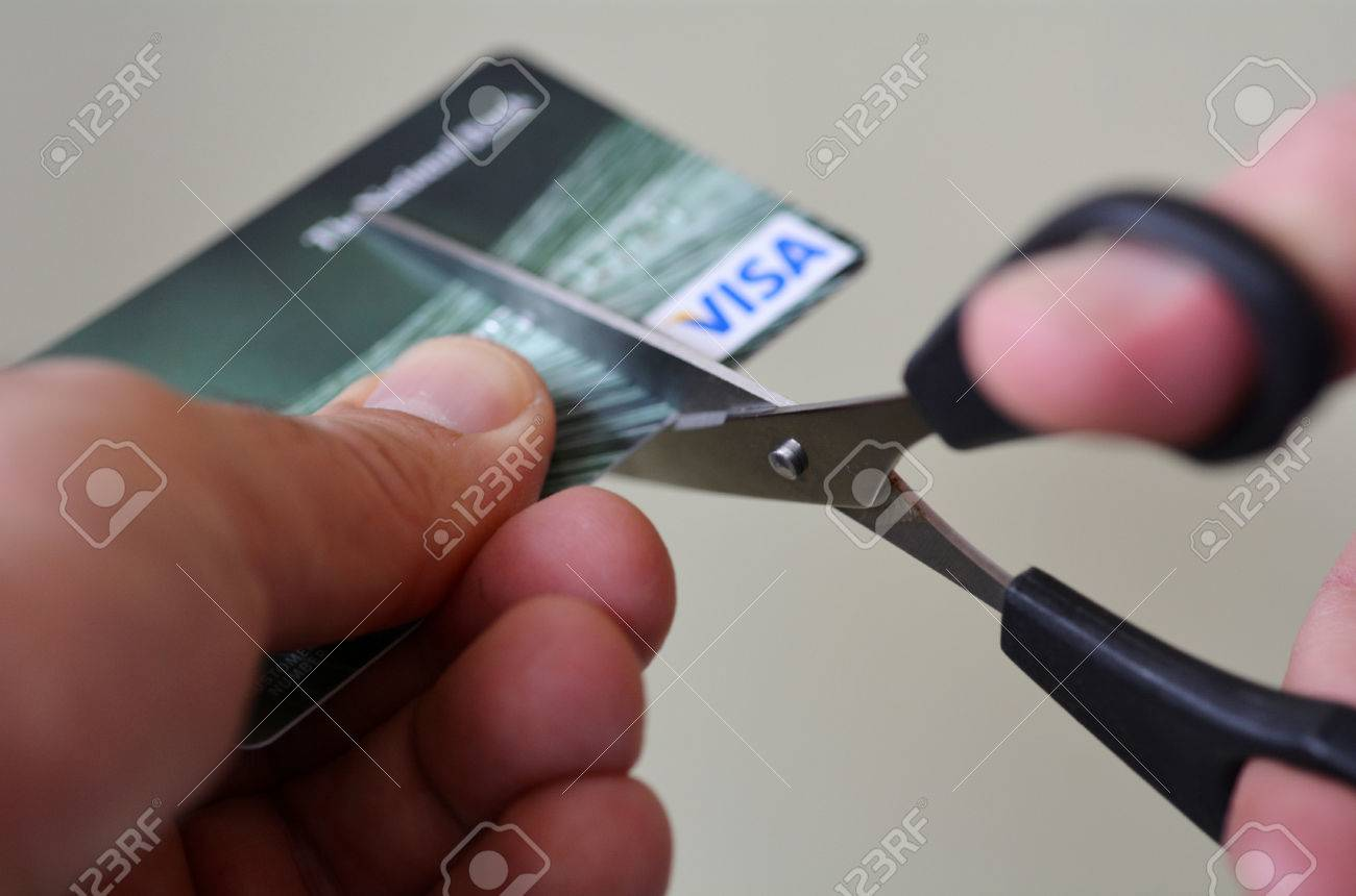 AUCKLAND - SEP 2014:Man hands cut creditcard with scissors.Minimum credit card payments are so low because it allows people to go into deeper debt. - 46257921