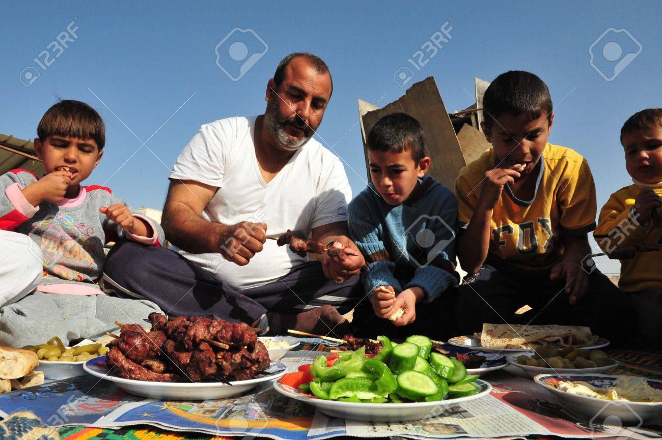 LAKIYA,ISR - DEC 12:Muslims eat lamb meat on Eid al-Adha, Dec 8 2008.The festival is celebrated by sacrificing a lamb or other animal and distributing the meat to relatives, friends, and the poor. - 46309778