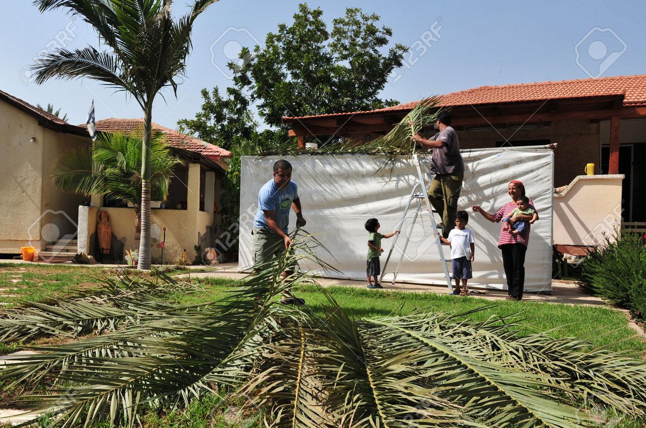 NETIVOT - OCTOBER02: Israeli Jewish family builds a Sukkah on the eve of the Jewish holiday, Sukkoth on October 02, 2009 in Netivot, Israel. - 46257625