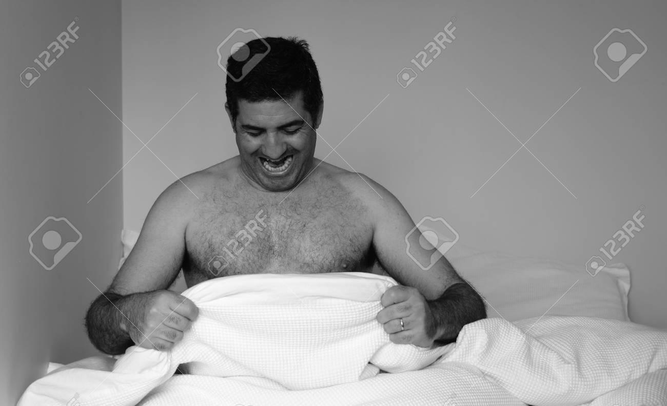 Gut Glücklicher Mann In Den Vierzigern (40er Jahre) Im Bett Blick Auf Seinen  Penis Unter Weißen Unten Erstreckt Blatt Im Schlafzimmer.
