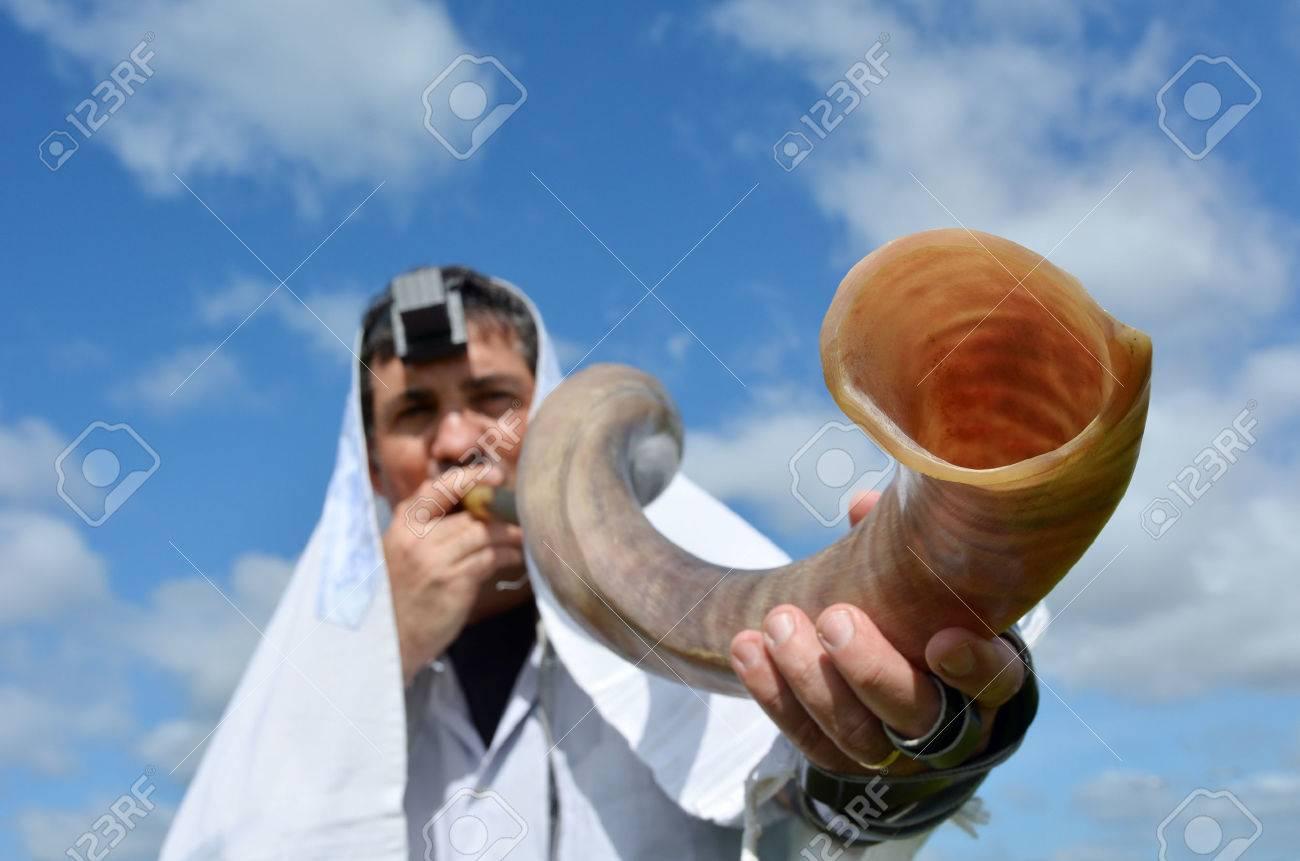 Jewish man blow Shofar outdoors under the sky, on the Jewish High Holidays in Rosh Hashanah and Yom Kippur - 48521777