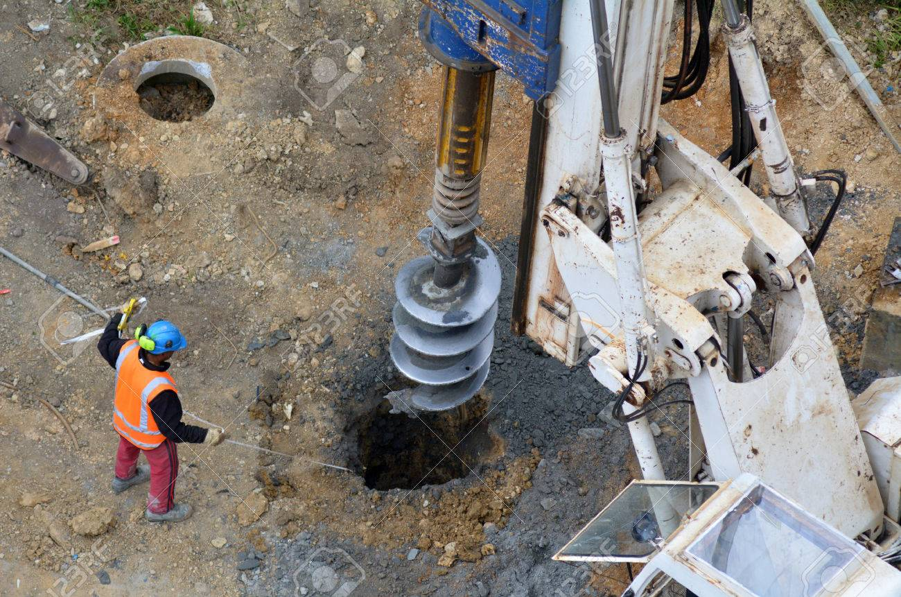 Aerial view of a worker measure the depth of a hole created by Hydraulic Hammer Drilling Machine at Construction Site. - 48521863