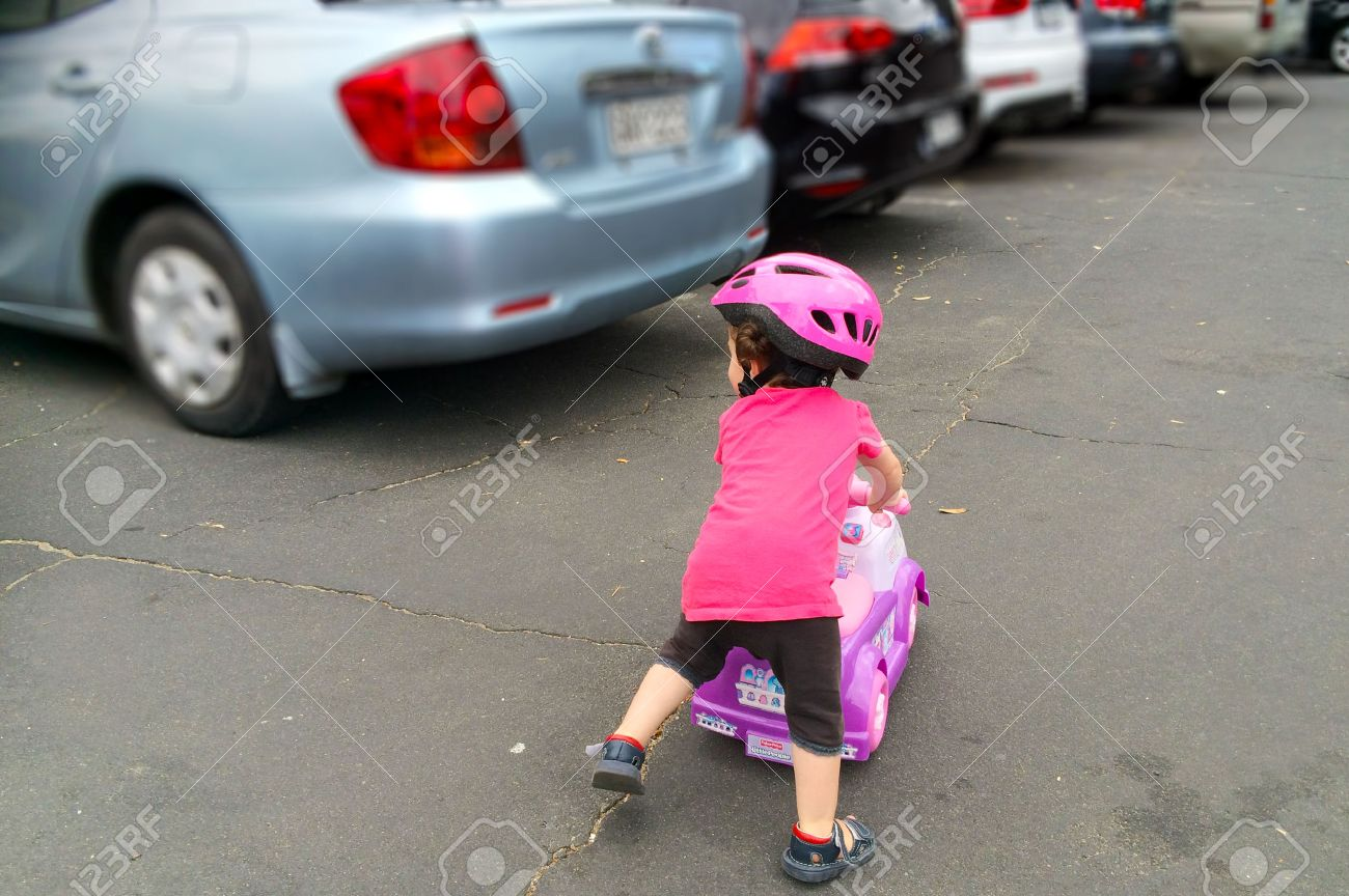 AUCKLAND - JAN 11 2016:Little girl (Naomi Ben-Ari age 1-2) rid a toy car in parking lot. The U.S. Center for Disease Control reported that about 300 fatalities per year result from backup collisions. - 50973098