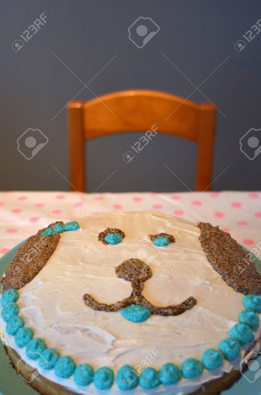 Homemade Birthday Cake In A Shape Of Dog Face On Table With Empty Chair