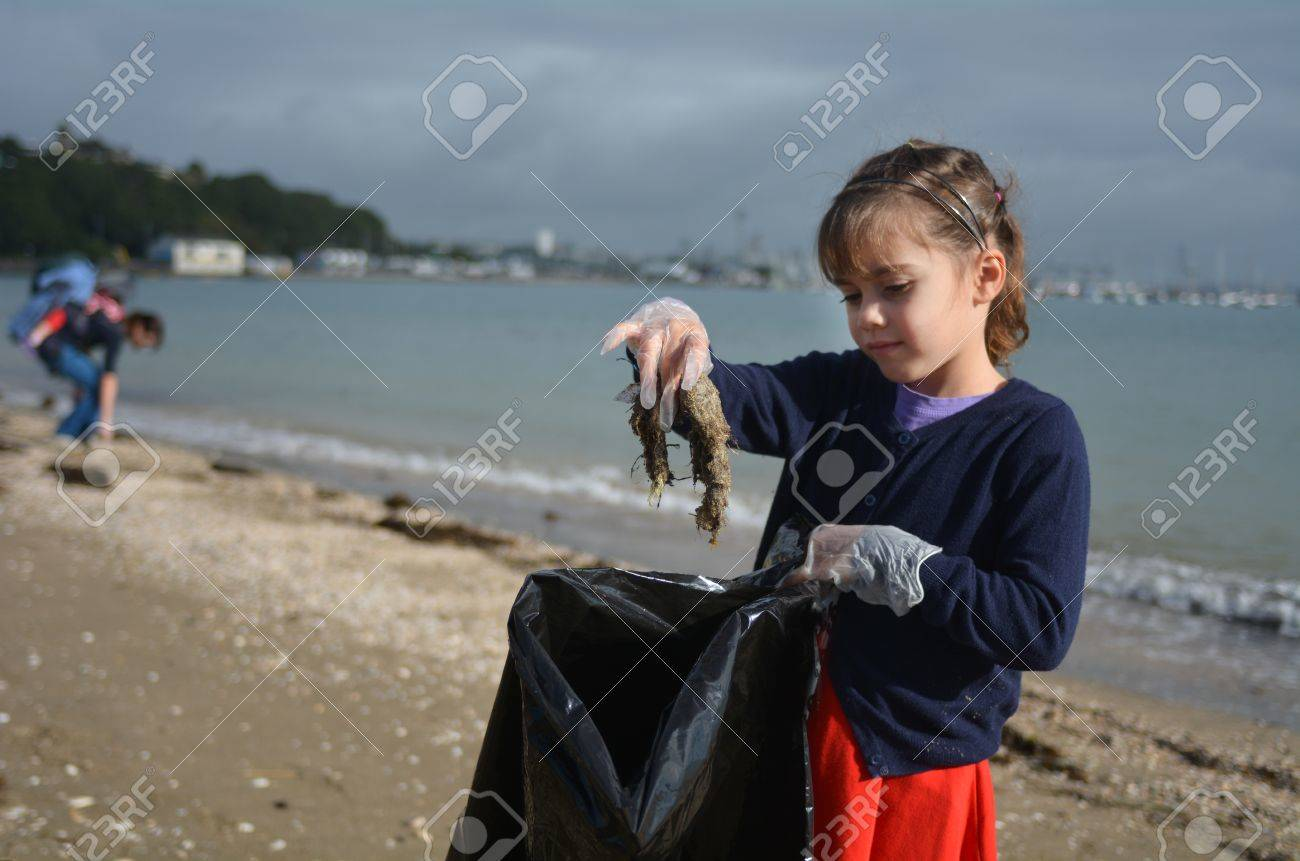 Little girl (age 6 ) pick up rubbish from the beach with her family. - 59138644